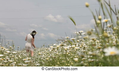 pregnant young woman walking away through chamomile meadow in spring