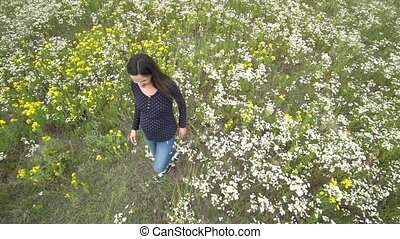 Pregnant young woman walking through chamomile field.