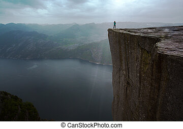 Preikestolen on a overcast day - girl is standing on the...