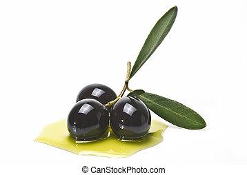 Premium black olives. - Olives with leaves on some olive oil...
