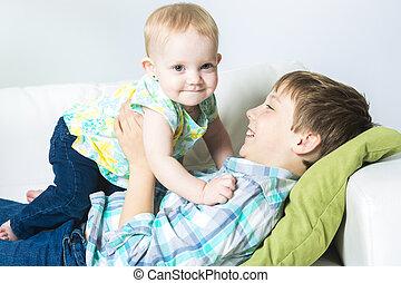 prendendo bebê, feliz, irmã, menino, sofá, seu