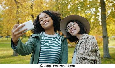 prendre, heureux, poser, appareil photo, sourire, selfie, utilisation, smartphone, parc, amis, filles