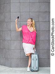 prendre, selfie, femme souriant, valise