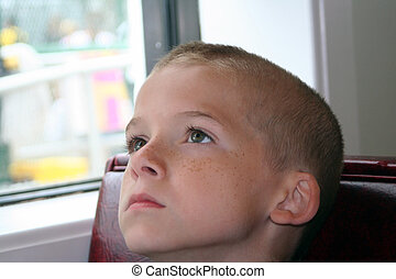 Closeup of the face of a serious looking boy looking upward, sitting in a restaurant booth next to a window.