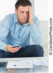 preocupado, casual, homem, segurando, calculadora, notas pagando