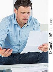 preocupado, casual, homem, segurando, calculadora, notas pagando, olhar, documento, em, luminoso, sala de estar