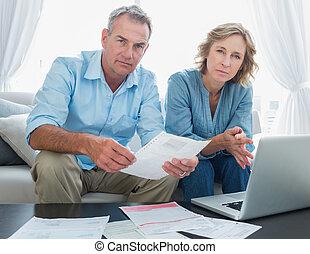 preocupado, par, pagar, seu, contas, online, com, laptop, olhando câmera, casa, em, a, sala de estar