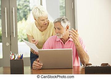 preocupado, par velho, usando computador portátil, casa