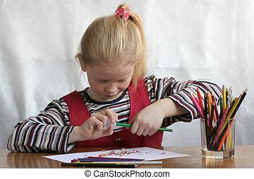 Preparation - A little girl sharpen her crayon