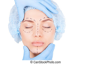 Preparation for facial surgery. Attractive young woman in medical headwear and sketches on face keeping eyes closed while doctor examining her face isolated on white