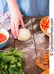 Raw dough in female hands, tomato sauce, food ingredients on a wooden table.