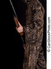Preparation for spring or autumn hunting. Hunter in camouflage clothing with a gun on a black background isolated. The man with the shotgun. Young guy in a camo suit with a gun.