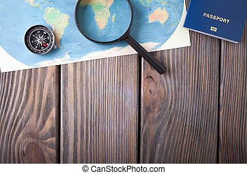 Preparation for Traveling concept, passport, compass, map on a wooden background.