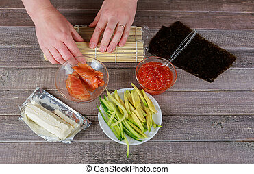 Preparation of a sushi roll in restaurant, Woman hands