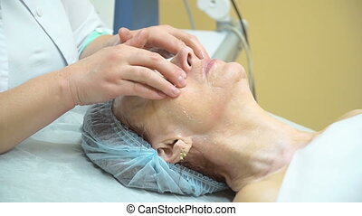 Preparation of an elderly woman for RF procedure lifting in a cosmetology clinic. Professional face massage.