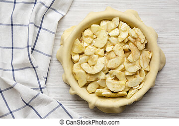 Preparation of apple pie on a white wooden table, top view. Overhead, from above, flat lay.
