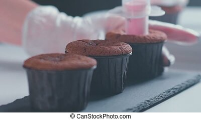 Preparation of cake. Add the stuffing. Close-up. Chocolate cupcake