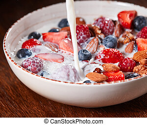 Preparation of dietary natural breakfast with fresh organic ingredients - berries, granola, nuts, honey and pouring milk in a white bowl on a wooden table.