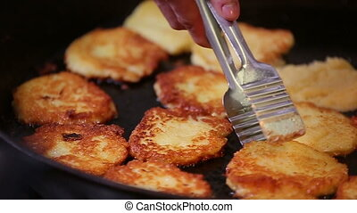 Preparation of golden crispy potato pancakes in a frying pan slowmotion