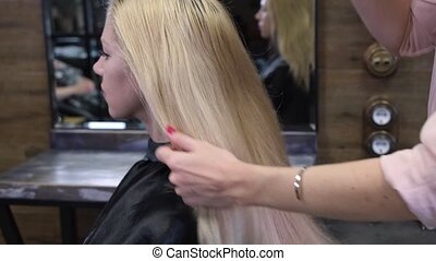 Preparation of hair model for dyeing. The hairdresser combs the blond hair before haircut. Beauty salon, hairdresser