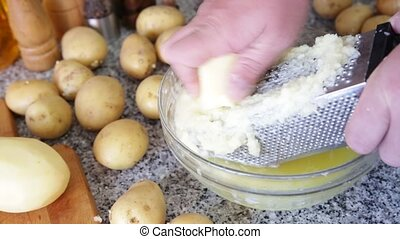 Shredding potato using grater, preparation of vegetable fritters. Home cooking