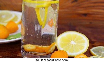 Preparation of lemonade. Cutting lemon pouring water.