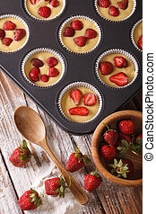 Preparation of muffins with fresh strawberries vertical top view