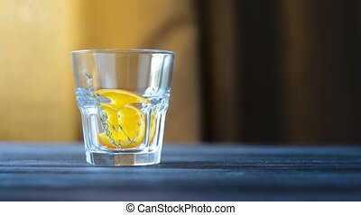 Preparation of one serving of lemonade or cocktail. Glass with slices of citrus and rosemary on dark wooden table. Slow refocusing. Cooking process