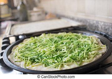 preparation of pizza with zucchini