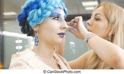 Preparation of the model for a photo shoot. The make-up artist adjusts her hair.