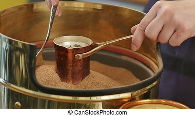 Preparation of Turkish coffee in copper Cezve on the hot...