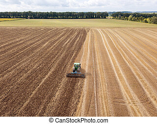 Preparatory work for sowing crops, cultivation of the soil by a tractor after harvesting in the summer time.