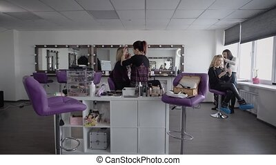 Prepare girls to prom shooting in a model school. Belles make up, make a stylish and trendy hairstyles, hair spray are applied, emphasize the cheekbones in a new dressing room with a large window