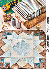 Prepared blocks for sewing quilt, stack of fabrics, sew accessories