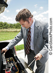A businessman whose car has broken down on the road. He's opening the trunk and looking at his toolchest.