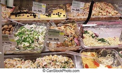 Prepared salads in the refrigerator on display - Prepared...
