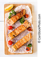 Prepared salmon fish fillets and grilled tomato, selective focus