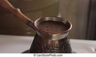 prepares traditional turkish coffee in copper pot over stove