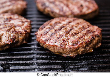 Preparing a batch of grilled ground beef patties or ...