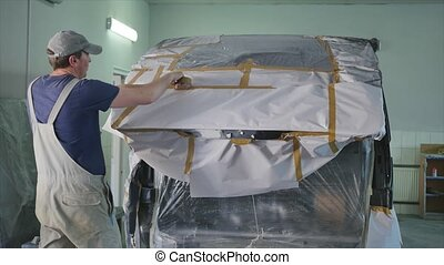 Preparing a car before spray painting.