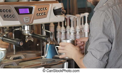 Handsome male barista making coffee and smiling while standing at the bar counter near the coffee machine. Barista cafe making coffee preparation service concept.