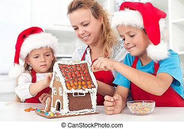 Preparing a gingerbread cookie house - Family preparing a ...