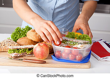 Preparing a lunch - Woman in blue t-shirt preparing a...