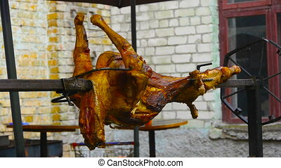 Preparing a ram on a spit, Juicy lamb carcass spins on a spit, grilled meat