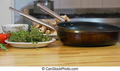 Preparing a roast - Pan over kitchen utensils, plates and...