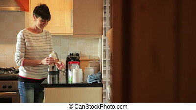 Preparing Baby Bottles - Mature woman is preparing powder ...