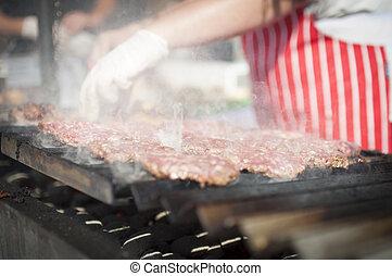 preparing beef burgers on grill