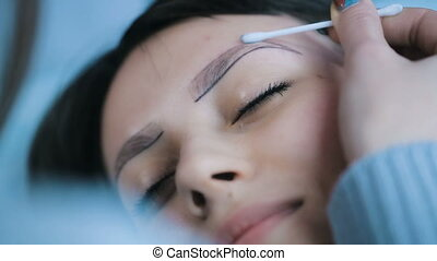 Preparing Before Eyebrows Tattooing - a woman draws eyebrows...