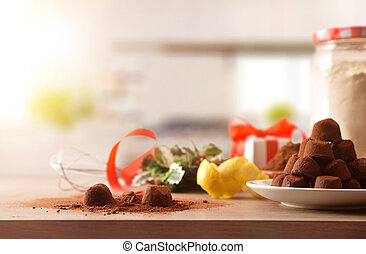 Preparing chocolate truffles on a kitchen table for Christmas holidays