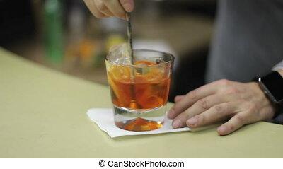 preparing cocktail with orange